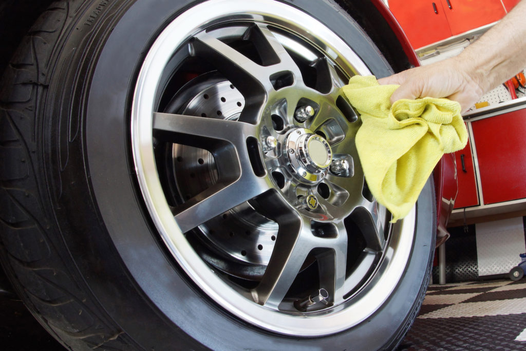 Hand polishing mag wheel with cloth in garage